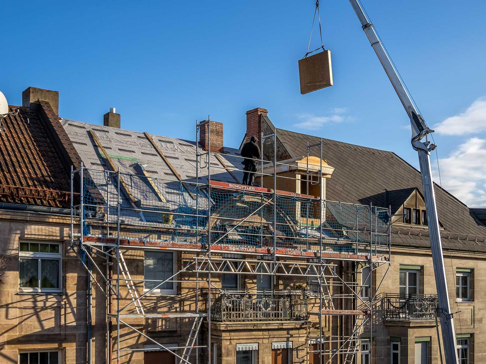 Eine wärmegedämmte und nach Maß vorgefertigte Dachgaube wird geliefert und mit einem Kran an das Dach angebaut.
