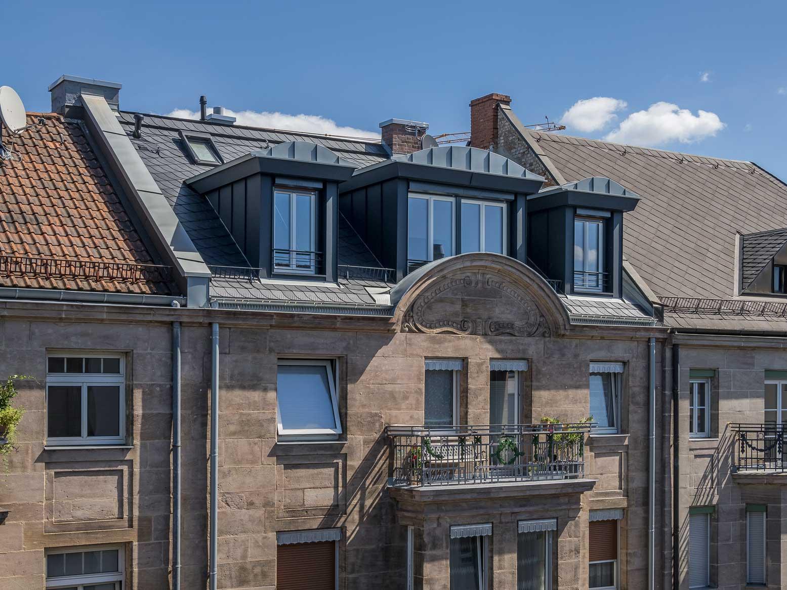 Drei schwarz verkleidete und gut gedämmte Dachgauben im Neubau-Stil.
