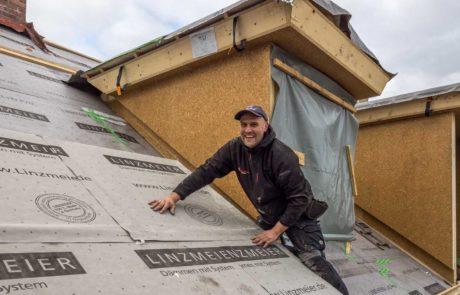 Ein Handwerker dämmt Dach mit Linzmeier Dämmungssystem